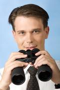 portrait of handsome ceo looking at camera and holding binoculars in hands - stock photo