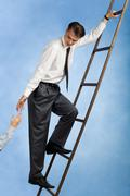 Image of confident professional going upwards the ladder and giving his hand to Stock Photos