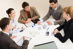 Group of five businesspeople discussing different questions gathered together ar Stock Photos