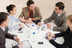 portrait of business people sitting around table and interacting - stock photo