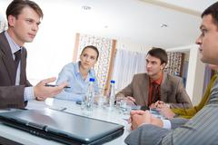 Photo of business team sitting around table and discussing new plan Stock Photos