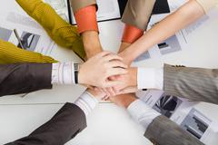 Close-up of pile of hands of business partners on working table Stock Photos