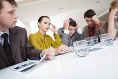 photo of several white collar workers brainstorming with pensive expressions - stock photo