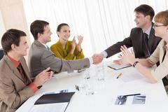 Image of confident partners shaking hands while their colleagues congratulating Stock Photos