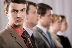 portrait of confident businessman looking at camera on background of row of his - stock photo