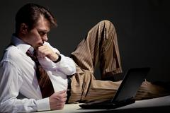 Photo of pensive businessman looking at laptop monitor and thinking of new idea Stock Photos