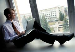 Photo of smart businessman sitting on window-sill with laptop and looking throug Stock Photos