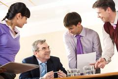 Happy boss listening to young businessman sharing his working idea Stock Photos