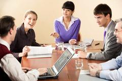 Portrait of successful business partners interacting during briefing in office Stock Photos