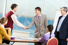 businessmen handshaking after signing documents at meeting - stock photo