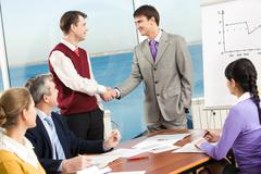 Stock Photo of portrait of successful business partners handshaking after negotiations