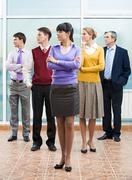 company of business partners standing and turning their heads aside with serious - stock photo