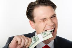 Close-up of strange businessman biting dollars by his teeth Stock Photos