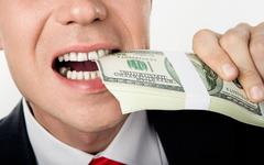 close-up of male's mouth biting bill of dollars - stock photo