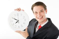 Photo of smiling employer with clock in hands looking at camera Stock Photos