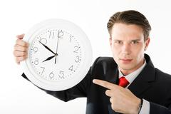 Stock Photo of businessman with serious expression on his face pointing at clock face