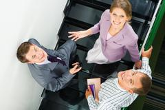 Image of business partners standing on staircase Stock Photos