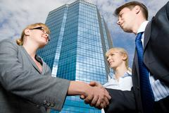 View from below of successful businesspeople handshaking as symbol of collaborat Stock Photos