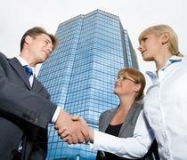Image of businessman shaking hand to confident woman with another female standin Stock Photos