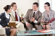 Stock Photo of portrait of business partners sitting on sofa and negotiating
