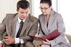 portrait of businessman and lady communicating while looking at document in the - stock photo
