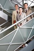 Portrait of smiling business partners standing behind railing and looking at cam Stock Photos
