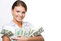 smiling business woman holding lots of dollars in hands - stock photo