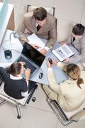 view from above of workplace with business team sitting around it and working - stock photo