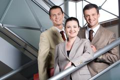 Portrait of happy businesswoman standing on staircase with two men behind Stock Photos