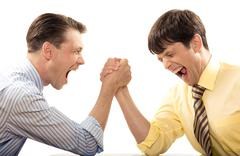 Portrait of emotional men screaming during arm wrestling competition Stock Photos