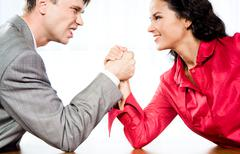 portrait of smiling woman and angry man fighting by their arms - stock photo
