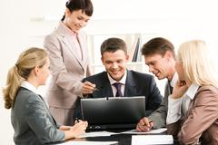 Portrait of friendly group sitting at table while three managers looking at lapt Stock Photos