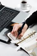 Above view of female hand writing in notepad with laptop and cup near by Stock Photos