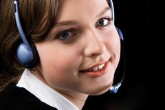 close-up of pretty woman face with headset looking at camera and smiling - stock photo