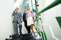 view from below of friendly team walking downstairs and looking straight while o - stock photo