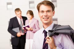 portrait of confident boss holding his jacket on the background of people - stock photo