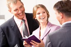 Happy woman standing between two businessmen and looking at one of them while la Stock Photos
