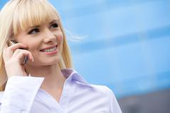 portrait of pretty blond woman speaking on mobile phone over blue background - stock photo