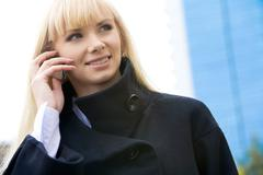 Stock Photo of portrait of elegant woman in black coat phoning outside