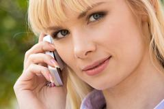 calling businesswoman looking at camera - stock photo