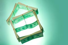 Conceptual photo of small house model made of us dollars over green background Stock Photos