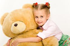 Portrait of cute little girl embracing her teddy bear and smiling Stock Photos
