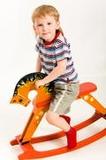 Photo of young boy sitting the toy orange horse Stock Photos