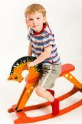 photo of young boy sitting the toy orange horse - stock photo