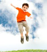 Photo of young boy jumping and raising hands in outside Stock Photos