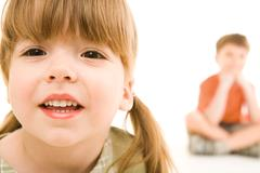face of small girl looking at camera on the background of her little brother - stock photo