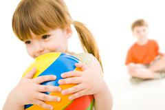 Photo of little girl holding colorful ball in hands with her brother at the back Stock Photos