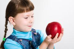 Portrait of little girl holding big red apple in hands and watching at it Stock Photos