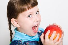 cute girl looking aside with widely open mouth ready to eat red juicy apple - stock photo