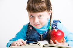 Portrait of little girl with red apple in hand and open book in front of her Stock Photos